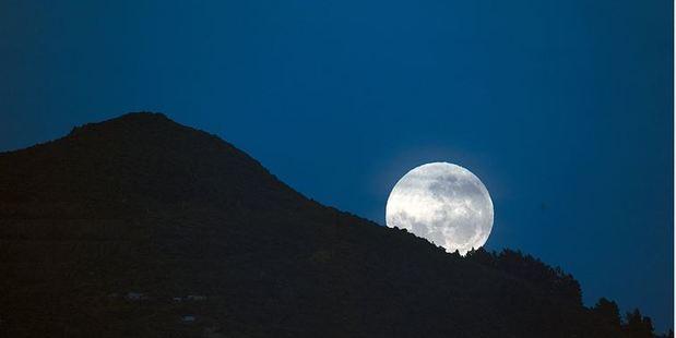 Loading On the eve of tonight's supermoon a near full moon sets behind Dunedin hills. Photo / Ian Griffin