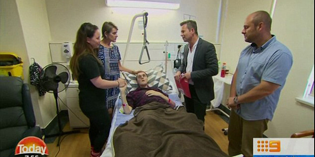 Jordan is pictured in bed flanked by his parents and holding his fiancée's hand. Photo / Nine News