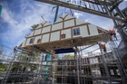 The 17-tonne roof of the Pop-up Globe comes to rest atop the three-storey structure. Photo / Peter Meecham