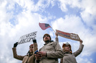 Demonstrators hold signs at Hartsfield-Jackson International Airport during a demonstration to denounce President Donald Trump's executive order on immigration. Photo / AP