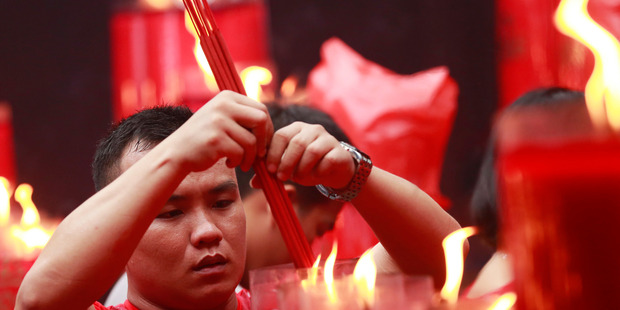 An ethnic Chinese man lights incense sticks at the Dharma Bakti Temple in Jakarta, Indonesia. Photo / AP