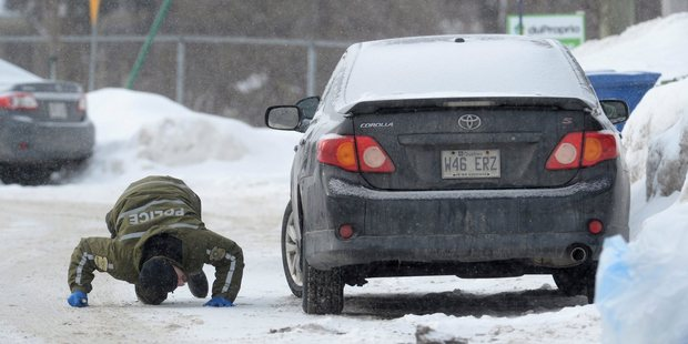 A police officer looks for evidence under a car in the area of a Quebec City mosque. Photo / AP