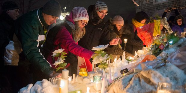 People place candles during a vigil in Quebec City. Photo / AP