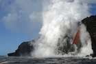 """A """"firehose"""" lava stream from Kilauea Volcano shoots out from a sea cliff on Hawaii's Big Island triggering massive explosions and giant waves"""