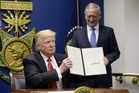US President Donald Trump signs executive orders as Defense Secretary Gen. James Mattis looks on in the Hall of Heroes at the Department of Defense. Photo / Getty