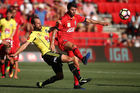 Andrew Durante of the Wellington Phoenix tackles George Mells of Adelaide United during their game in searing conditions. Photo / Getty