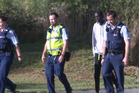 Police officers walk the banks of the Hutt River, with an unidentified man, near where a swimmer went missing last night. Photo / Mark Mitchell