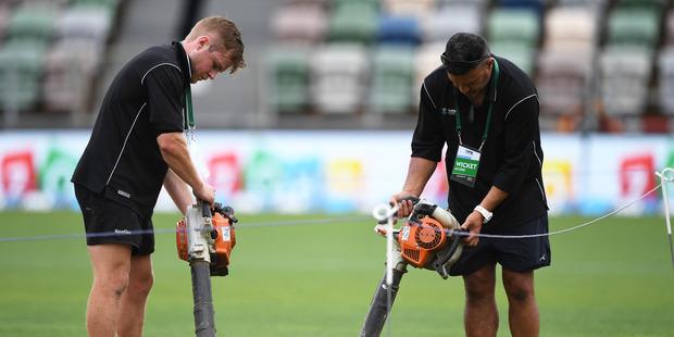 Ground staff try to dry the wicket area. Photo / www.photosport.co.nz