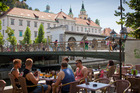 A group of tourists drink beer on the banks of a waterway in central Ljubljana, Slovenia. Photo / AP