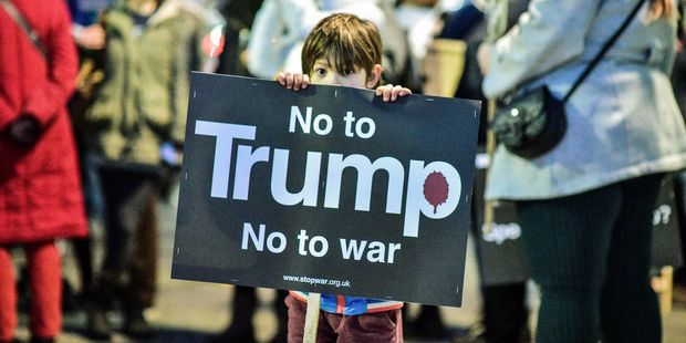 A young boy holds a placard during a protest against Donald Trump's inauguration as U.S. president in Bristol, England. Photo / AP