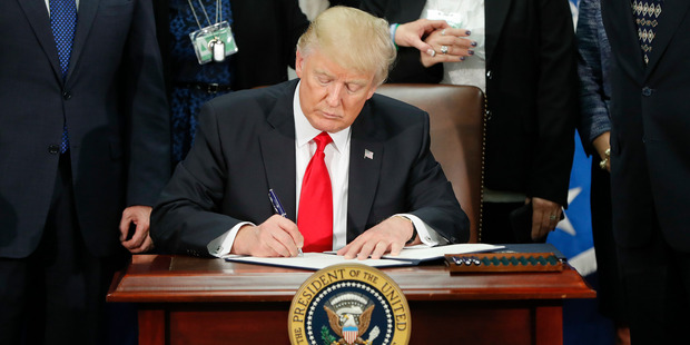 President Donald Trump signs an executive order for border security and immigration enforcement improvements has had an immediate impact on some travellers. Photo / AP