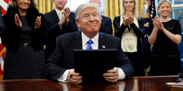 President Donald Trump smiles after signing executive actions. Photo / AP