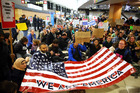 Demonstrators sit down in the concourse and hold a sign that 'We are America' as more than 1000 people gather at Seattle-Tacoma International Airport. Photo / AP