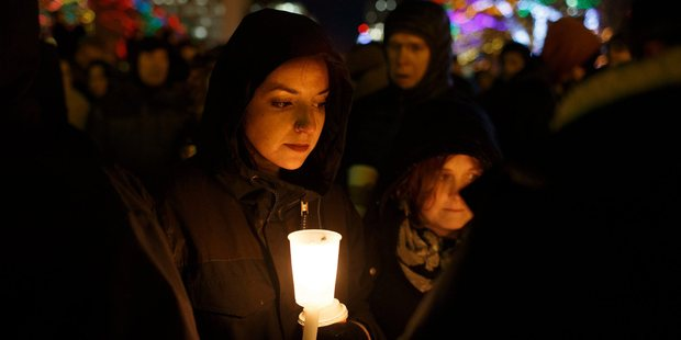 A woman joins others as they gather in remembrance of the victims of Sunday's shooting at a Quebec City mosque, during a vigil in Edmonton, Alberta. Photo / AP