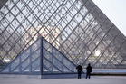 Police officers patrol at the pyramid outside the Louvre museum in Paris. Photo / AP