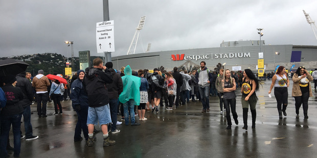 Guns N' Roses fans waited in the rain outside Westpac Stadium in Wellington on Thursday after a malfunction with the gate system. Photo / Supplied