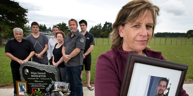 Judy Richards (foreground) pictured holding a photograph of her son Rhys Middleton while other family members gather around the headstone at his graveside in Tauranga. Photo/NZME
