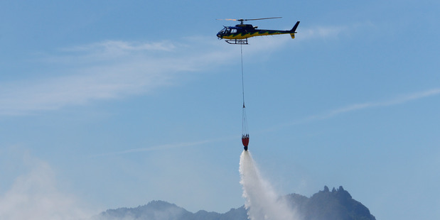 A helicopter uses a monsoon bucket to fight yesterday's scrub fire that had the potential to endanger lives and properties in Ruakaka. PHOTO/MICHAEL CUNNINGHAM
