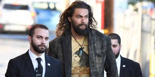 Actor Jason Momoa towers over two of his bodyguards.