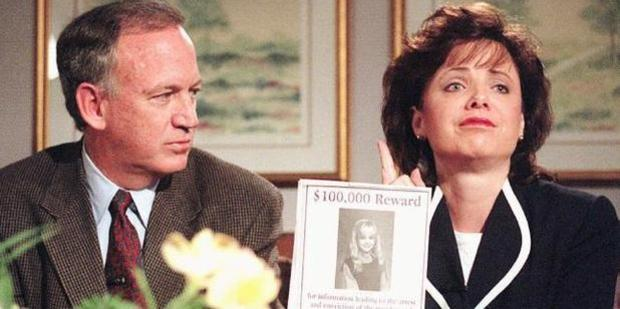 John Ramsey looks on as his wife Patsy holds an advertisement promising reward for information leading to arrest and conviction of murderer of their daughter JonBenet. Photo / AP