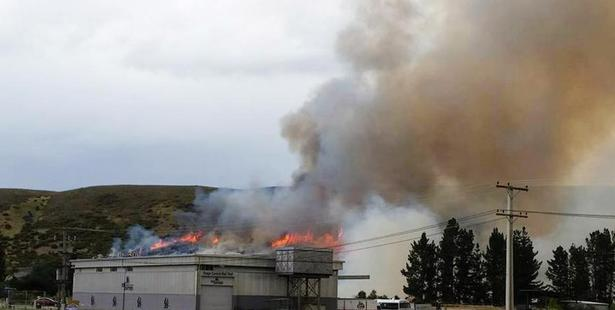 Fire burns on a hillside behind a building at the western end of the Otago Central Rail Trail near Clyde yesterday. Photo: Kristy Velenski