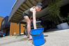 Kristen Andrew from Mount Maunganui is doing her bit to conserve water by washing her car with a bucket. Photo / George Novak