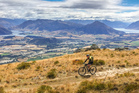 Michael Brown rides in the high country above Lakes Wanaka and Hawea during stage six a 66km journey that climbed 2000m during the 7 day Pioneer Mountain Bike ride. Photo / Greg Bowker