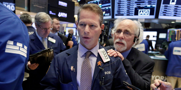 Trader Robert Charmak, center, and Peter Tuchman, right, work on the floor of the New York Stock Exchange. Photo / AP
