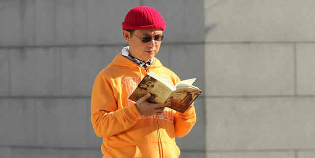 In this December 2013, photo, Xiao Jianhua, a Chinese-born Canadian billionaire, reads a book outside the International Finance Centre in Hong Kong. Photo / AP file
