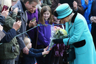 The Queen stops to receive flowers from 3-year old Jessica Atfield in West Newton, England. Photo / AP