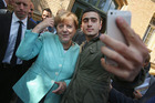 German Chancellor Angela Merkel poses for a selfie with Syrian refugee Anas Modamani. The selfie is the centre of a lawsuit Modamani has launched against Facebook. Photo / Getty