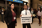 Volunteer attorneys, Yalda Satar (L) and Kapesh Patel stationed at Los Angeles International Airport wait to assist travelers. Photo / Getty