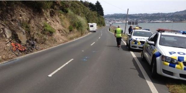 Police interview people after a campervan and cyclist collided in Dunedin today. Photo / Otago Daily Times, Shawn McAvinue