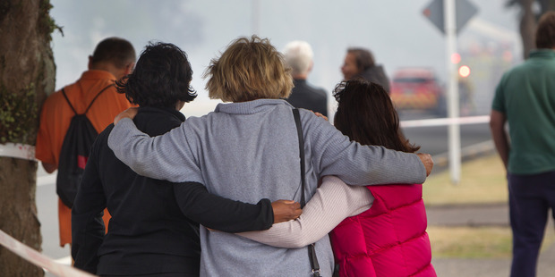 Devastated members of the public look on.  Photo/Ben Fraser