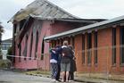 People hug outside the devastated St John's Church. Photo/Ben Fraser