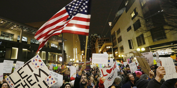 """A protester waves a U.S. flag as another holds a sign that reads """"Let Them In"""" during a march and rally to oppose President Donald Trump. Photo / AP"""