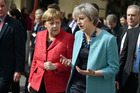 British Prime Minister Theresa May, center right, speaks with German Chancellor Angela Merkel, center left, as they walk during an event at an EU summit in Valletta. Photo / AP