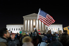 Protester waves an American flag in front of the Supreme Court during a protest about President Donald Trump's recent executive orders in Washington. Photo / Alex Brandon