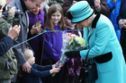 Britain's Queen Elizabeth II stops to receive flowers from 3-year old Jessica Atfield, after the queen and her husband Duke of Edinburgh, attended church on Sunday. Photo / AP