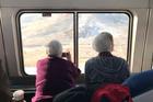 Two women take photos of the Sierra Nevada mountains on the California Zephyr train. Photo / AP