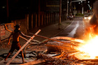 A man sets a street barricade ablaze in the city of Vitoria. More than 1000 army troops are patrolling the southeastern Brazilian city after violence erupted there. Photo / AP