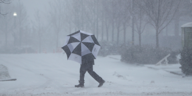A person in Jersey City, New Jersey, shields themselves from falling snow with an umbrella. Photo / AP