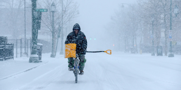 Loading Angel Ares, of Hartford, Connecticut, bikes up Park Street on his way to shovel snow at buildings he takes care of in the Frog Hollow section of the city. Photo / AP