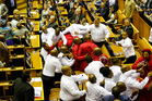 Economic Freedom Fighters, dressed in red, are forcibly removed from parliament in Cape Town, South Africa. Photo / AP