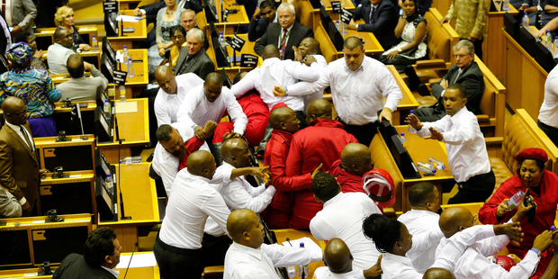 Loading Economic Freedom Fighters, dressed in red, are forcibly removed from parliament in Cape Town, South Africa. Photo / AP