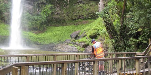 """A Waikato Regional Council staff member tests the """"unusual"""" water colour of Bridal Veil Falls yesterday. Photo / Waikato Regional Council"""