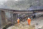 KiwiRail staff inspect one of the damaged bridges. Photo / Supplied