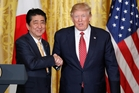 Was Shinzo Abe ready for Donald Trump's special style of shaking hands? Photo / AP
