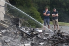 Simon Grace, right, and his brother watch as the remains of the family home are dampened down. Photo / Alan Gibson