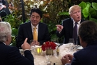 Shinzo Abe and Donald Trump joke with New England Patriots owner Robert Kraft (left) during dinner at the Mar-a-Lago. Pihoto / AP